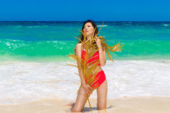 Young beautiful Asian girl in red cloth wiht palm leaf on the be Stock Image