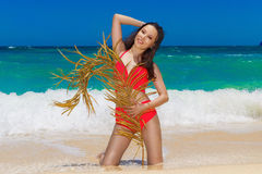Young beautiful Asian girl in red cloth wiht palm leaf on the be Stock Images