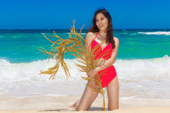 Young beautiful Asian girl in red cloth wiht palm leaf on the be Stock Photos