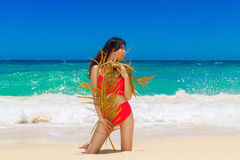 Young beautiful Asian girl in red cloth wiht palm leaf on the be Royalty Free Stock Photo