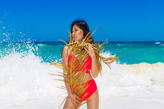Young beautiful Asian girl in red cloth wiht palm leaf on the be Stock Photo