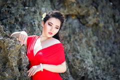 Young beautiful Asian girl in red dress on the beach of a tropic Stock Photo