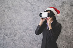 Young beautiful Asian girl wearing a festive Christmas hat. While playing a virtual reality game Stock Image