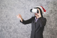 Young beautiful Asian girl wearing a festive Christmas hat. While playing a virtual reality game Royalty Free Stock Photo