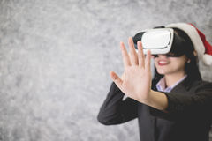 Young beautiful Asian girl wearing a festive Christmas hat. While playing a virtual reality game Stock Images