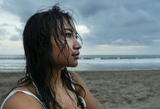 Young beautiful Asian girl with wet hair at sunset beach looking in the distance thoughtful and pensive Stock Images