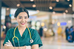 Young beautiful Asian medical Dr wearing green scrubs. With blurred busy background royalty free stock image
