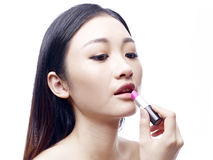 Young and beautiful asian model applying lipstick Stock Image