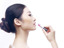Young and beautiful asian model applying lipstick Stock Images