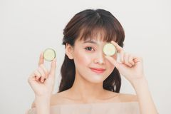 Young beautiful asian teenger holding slices of cucumber near he. R face Royalty Free Stock Photo