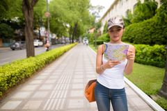 Young beautiful Asian tourist woman reading map in Vietnam. Portrait of young beautiful Asian tourist woman exploring Ho Chi Minh city in Vietnam royalty free stock photography