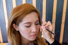 Young beautiful asian woman applying make-up Stock Images