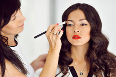 Young beautiful asian woman applying make-up by make-up artist stock photography