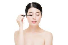 Young beautiful asian woman applying mascara on eyelashes Stock Photos