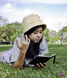 Young beautiful asian woman with book. Young beautiful asian woman lies on green summer meadow with book Stock Image