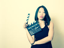 Young beautiful asian woman with clapperboard vintage colors por Royalty Free Stock Photos