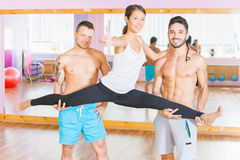 Young beautiful asian woman doing split between two guys Stock Photos