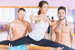 Young beautiful asian woman doing split between two guys Royalty Free Stock Photo
