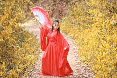 Free Young Beautiful Asian Woman Dress In Traditional Chinese Old Fashion Warrior Style With Ancient Fan. Cute Girl In Red Dress Standi Stock Photography - 200054572