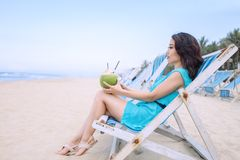 Young beautiful asian woman is drinking coconut juice on the beach Royalty Free Stock Photo