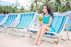 Young beautiful asian woman is drinking coconut juice on the beach Stock Photo