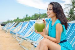 Young beautiful asian woman is drinking coconut juice on the beach Stock Photos