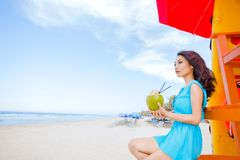 Young beautiful asian woman is drinking coconut juice on the beach Royalty Free Stock Image