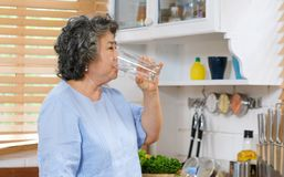 Free Young Beautiful Asian Woman Drinking Water While Standing By Window In Kitchen Background, People And Healthy Lifestyles Royalty Free Stock Images - 161409099