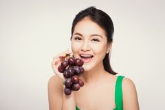 Young beautiful asian woman eating fresh grapes isolated on whit. E background Stock Photography