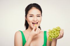 Young beautiful asian woman eating fresh grapes isolated on whit. E background Royalty Free Stock Photography