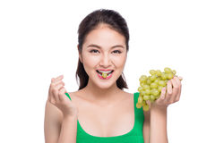 Young beautiful asian woman eating fresh grapes isolated on whit Stock Images