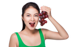 Young beautiful asian woman eating fresh grapes isolated on whit Royalty Free Stock Photography