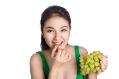 Young beautiful asian woman eating fresh grapes isolated on whit Royalty Free Stock Photo