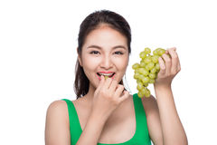 Young beautiful asian woman eating fresh grapes isolated on whit Royalty Free Stock Photos