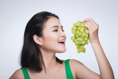 Young beautiful asian woman eating fresh grapes isolated on white background stock images