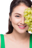Young beautiful asian woman eating fresh grapes  on whit Stock Images