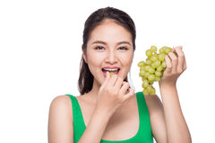 Young beautiful asian woman eating fresh grapes  on whit Stock Photos