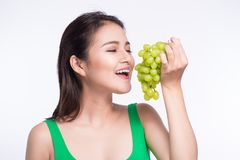 Young beautiful asian woman eating fresh grapes  on whit Royalty Free Stock Photo