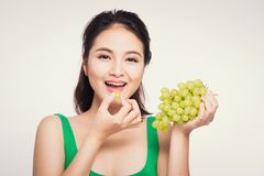 Young beautiful asian woman eating fresh grapes on white background royalty free stock photography