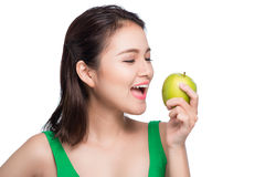 Young beautiful asian woman eating fresh green apple on white ba Stock Photos