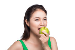 Young beautiful asian woman eating fresh green apple on white ba. Ckground Royalty Free Stock Photos