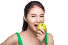 Young beautiful asian woman eating fresh green apple on white ba. Ckground Stock Image