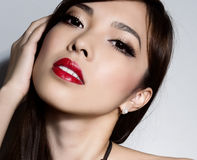 Young beautiful asian woman with flawless skin and perfect make-up and brown hair. Sexy Lipstick, highlighter and rouge on clear skin Royalty Free Stock Image