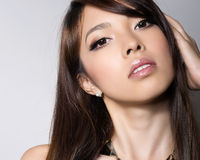 Young beautiful asian woman with flawless skin and perfect make-up and brown hair Royalty Free Stock Photography