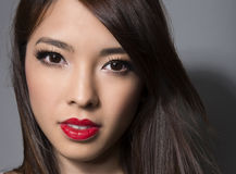 Young beautiful asian woman with flawless skin and perfect make-up and brown hair Stock Photos