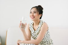 Young beautiful asian woman holding a glass of water while sitti stock photo
