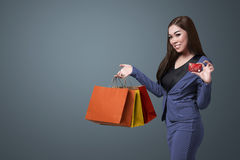 Young beautiful asian woman holding shopping bags and show her c Stock Image