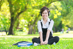 Young beautiful Asian woman listening music in headphones Royalty Free Stock Photo