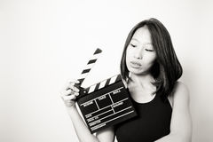Young beautiful asian woman looking at  clapperboard black and w Royalty Free Stock Photo