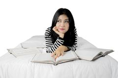 Young beautiful Asian woman reading in bed Royalty Free Stock Photo
